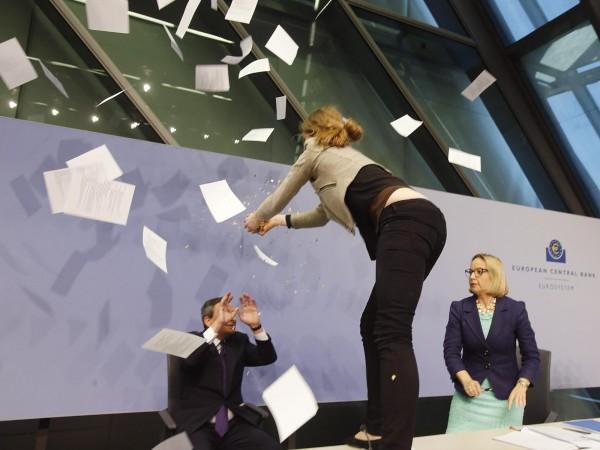 """Clamorosa contestazione alla conferenza stampa di Draghi: donna salta sul palco lanciando coriandoli """"contro la dittatura della Bce"""""""